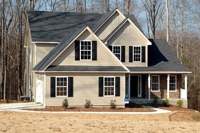 světlý dům, tmavá střecha, neupravený terén